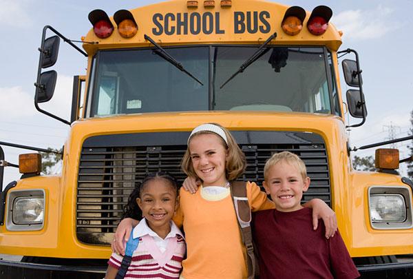 Kids in front of a school bus.